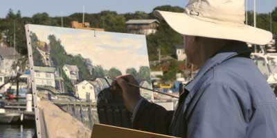 Man in a white hat painting a beautiful picture of Gloucester's harbor.