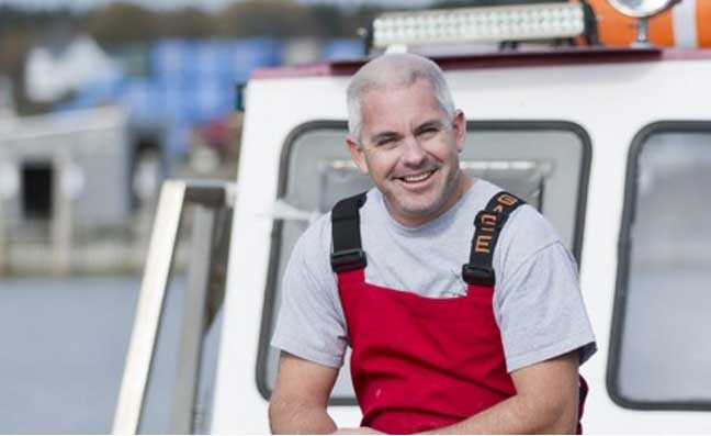 Fisherman sitting on a boat with red overalls.