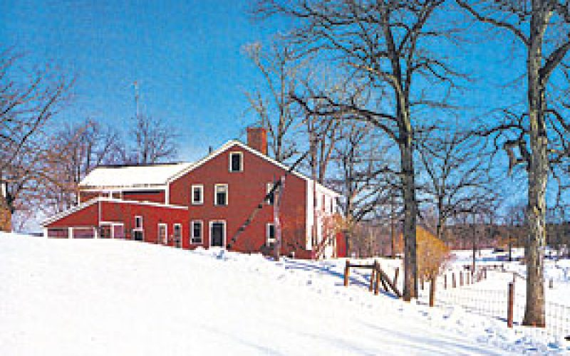 Red house covered in snow known as the John Greenleaf Whittier Birthplace.