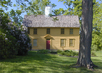 Yellow Home with big tree in front yard. This house is called the Parson Barnard House.