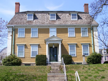 The Sargent House Museum has stone stairs leading to the front door. It is yellow with two chimneys on opposite ends of house.