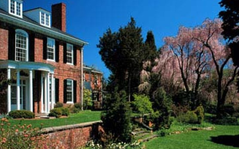 Brick house with green lawn in front known as Long Hill and Sedgwick Gardens.