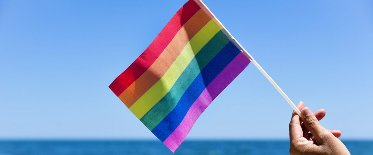 man on beach holding rainbow pride flag