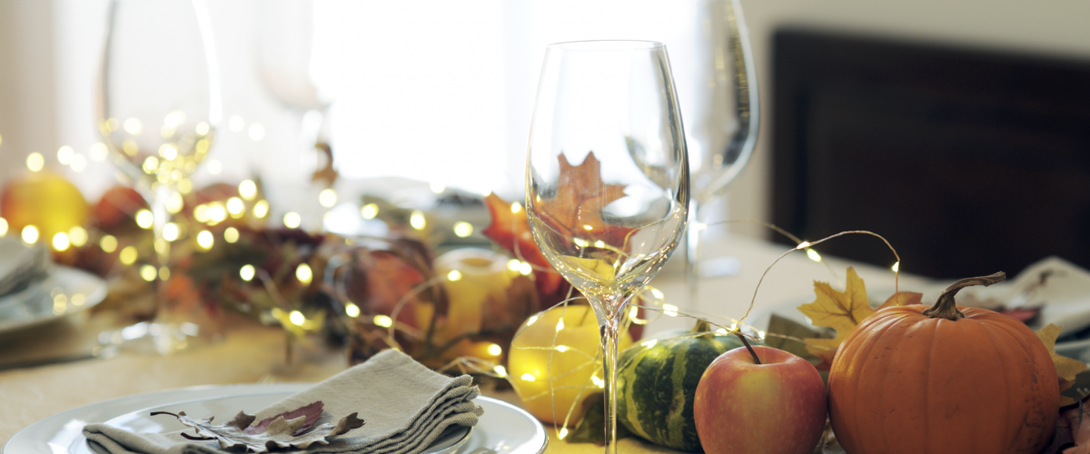 Thanksgiving dinner table set with wine glasses, pumpkins and dining ware