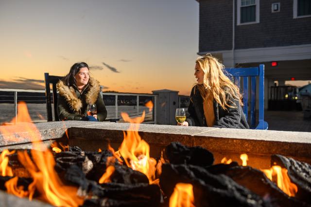 women sitting by fire pit