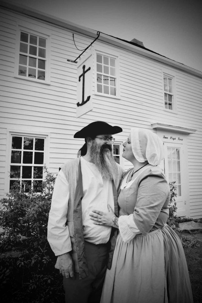 People in costume in front of historic home
